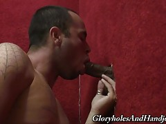 Oh wow, do you see that big black dick poking through the hole in the wall? That fucking thing is huge! I don`t know if I could even wrap my lips around it let alone deepthroat it. I want to give it a try so here goes nothing. Yummy, it tastes just like c